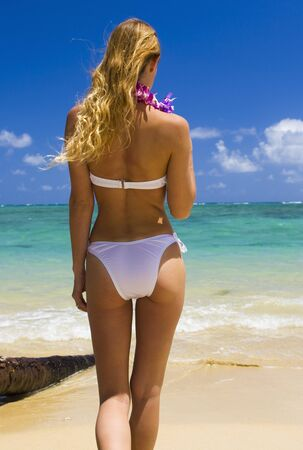 a beautiful young blond woman in a bikini at a tropical beach