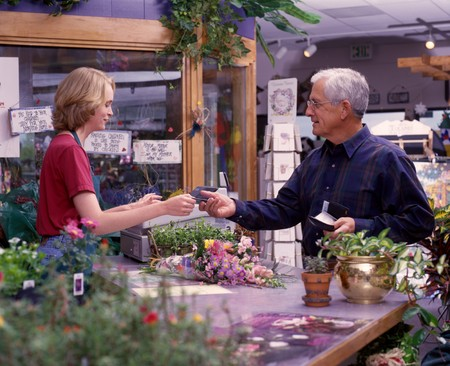 a senior man buying flowers at a garden shop