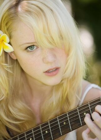 beautiful young blond woman playing her guitar outdoors Stock Photo - 4490744