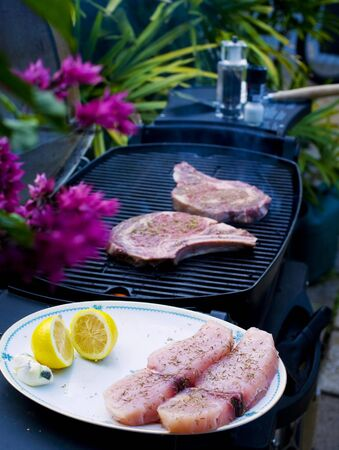 ribeye steaks cook on the bar-b-que grill while swordfish steaks next