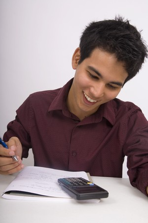 A young Asian American man doing his homework with a calculator Stock Photo - 4490746
