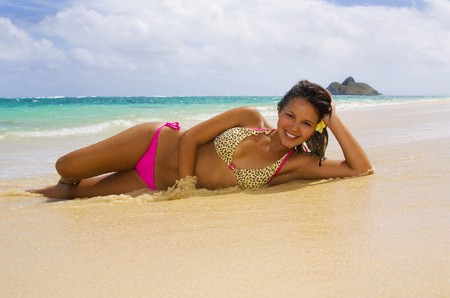 a beautiful young Polynesian girl in a pink bikini lying on a Hawaii beach
