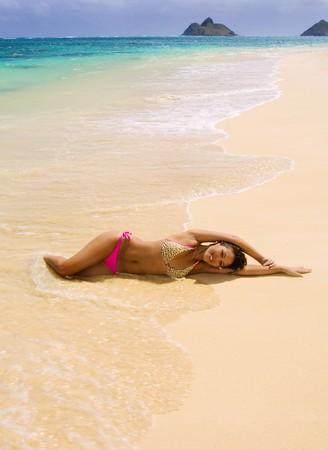 a beautiful young Polynesian girl in a pink bikini lying on a Hawaii beach