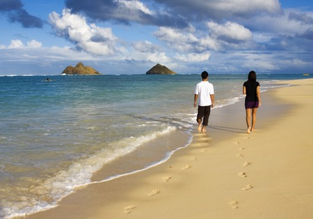 walk in: A young couple walk by the waters edge on a beach in hawaii