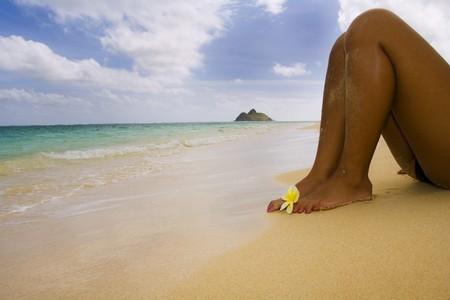 Legs of a Polynesian girl on a secluded Hawaii beach with a flower Stock Photo
