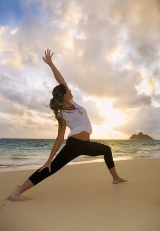 solo form: Young woman doing yoga at the beach in Hawaii at daybreak