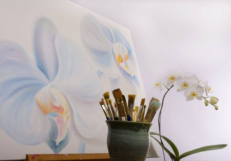 painting of phalaenopsis orchids with artists brushes in the foreground