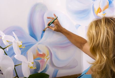 A female artist painting phalaenopsis orchids on canvas in her studio