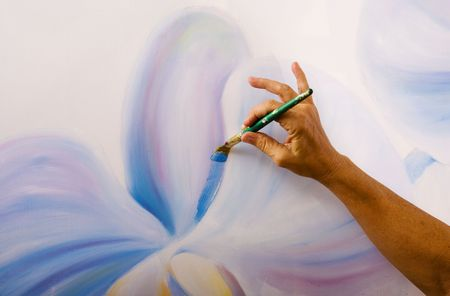 A hand of a female artist painting orchids on canvas in her studio