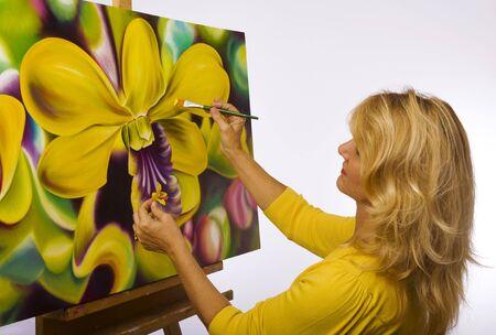 Een vrouwelijke kunstenaar schilderij Dendrobium orchideeën op doek in haar atelier