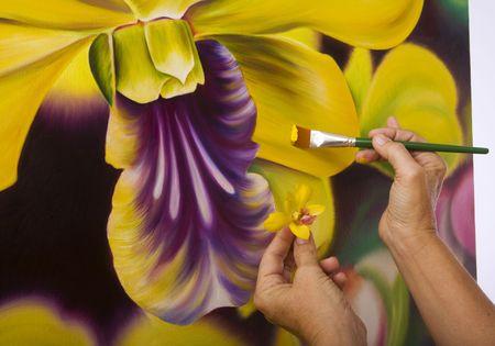 hand schilderen: handen van een vrouwelijke kunstenaar schilderij orchideeën op doek in haar atelier