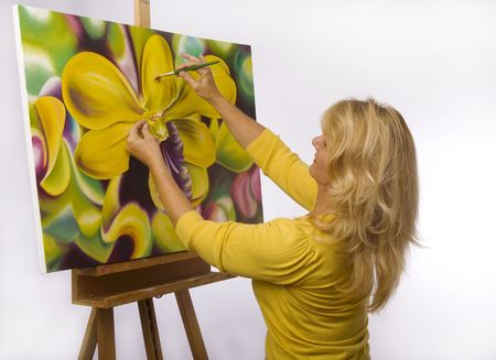 dendrobium: A female artist painting dendrobium orchids on canvas in her studio