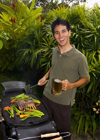 Asian American man grilling rack of lamb on a bar-b-que in his yard Stock Photo