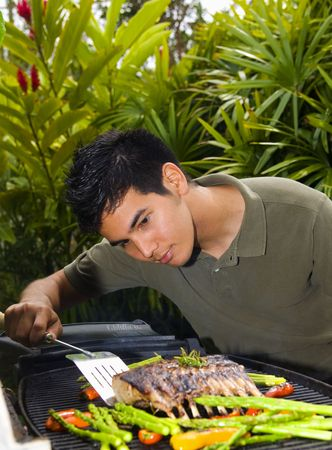 Asian American man grilling rack of lamb on a bar-b-que in his yard photo