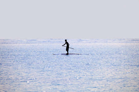 Silhouette of a man standing on a paddle board
