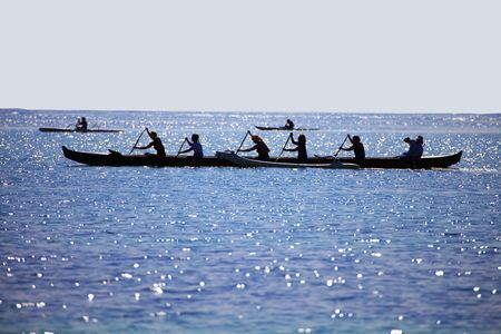 Silhouette of women paddling an outrigger canoe