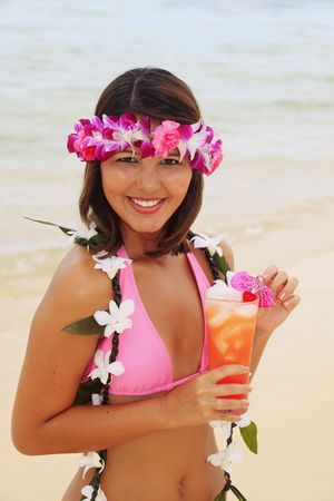 Polynesian girl with flower lei in a pink bikini at the beach with a drink photo