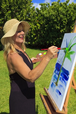 female artist in her fifties creating a painting outside on canvas