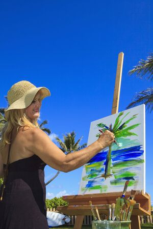 female artist in her fifties creating a painting outside on canvas photo