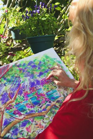 A female artist in her fifties painting with pastels in her garden