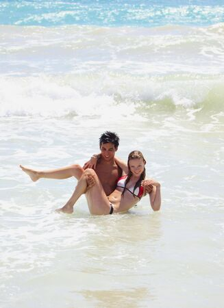young couple plays in the surf at kailua Beach, Hawaii photo