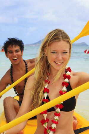 A young couple paddle a kayak in Hawai Stock Photo