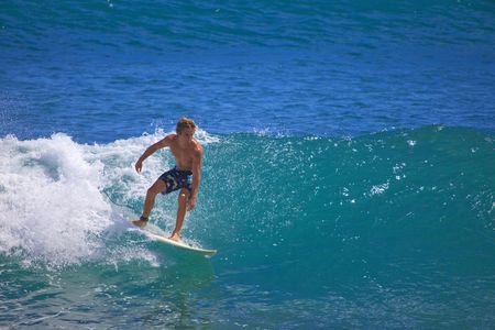 young man catches a wave on his surfboard at Point Panic, Oahu, Hawaii photo