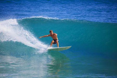 Młody człowiek połowy fali na jego deskę surfingową na Panic Point, Oahu, Hawaii