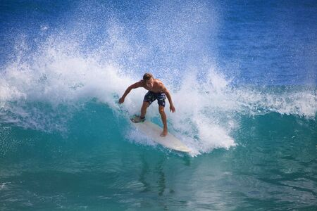 young man catches a wave on his surfboard at Point Panic, Oahu, Hawaii