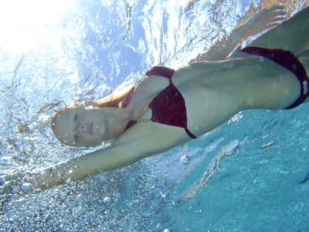 young blond girl in a red bikini swims freestyle in a pool