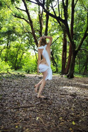 wood nymph: woman in white chiffon playing in a tropical forest like a wood nymph