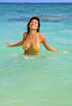 busty: jonge vrouw in een gele bikini in de oceaan op Hawaï Stockfoto