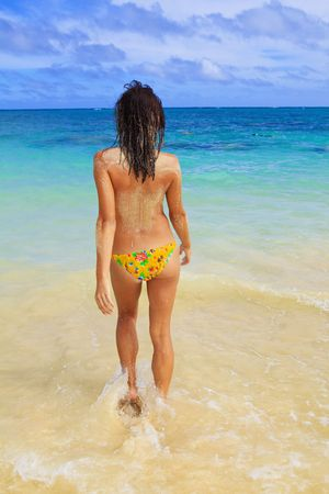 beautiful young woman in a yellow bikini at the beach at lanikai walking topless into the ocean to wash off the beach sand Stock Photo