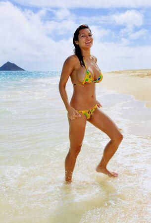 beautiful young woman in a yellow bikini at the beach at lanikai