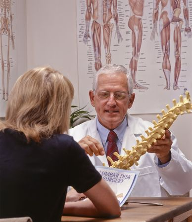 chiropractic doctor showing spine to a patient