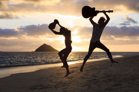 silhouette of twin brothers with drum and guitar leaping in the air at sunrise on a hawaii beach