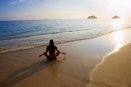 hawaii sunset: beautiful young woman doing yoga and meditation at the beach at sunrise in Hawaii Stock Photo
