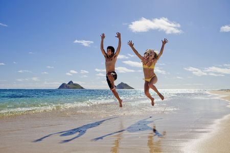 young couple leaping for joy on a hawaii beach photo