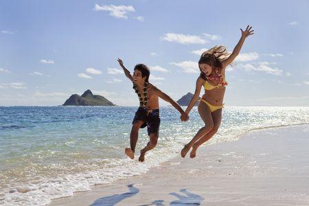 MÅ'oda para leaping dla radoÅ›ci na plaży Hawaje Zdjęcie Seryjne