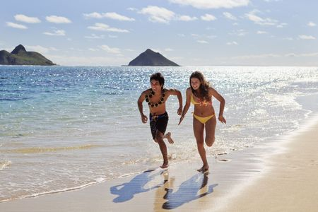 young couple running on the beach in hawaii Stock Photo - 6501223