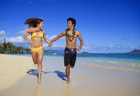 bikini couple: young couple running on the beach in hawaii