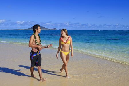 pacific island man plays ukulele for a young woman on a hawaii beach photo