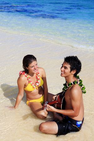 pacific island man plays his ukulele for young woman on a hawaii beach photo
