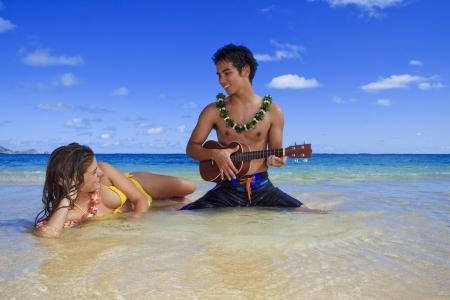Mężczyzna Wyspy Pacyfiku odgrywa jego ukulele za młoda kobieta na plaży hawajski