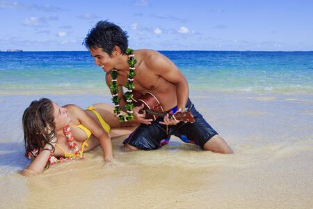 pacific island man plays his ukulele for a young woman on a hawaii beach photo
