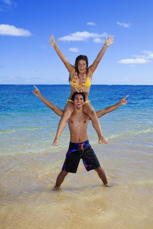 carrying: young woman in bikini sits on the shoulders of an island man in hawaii