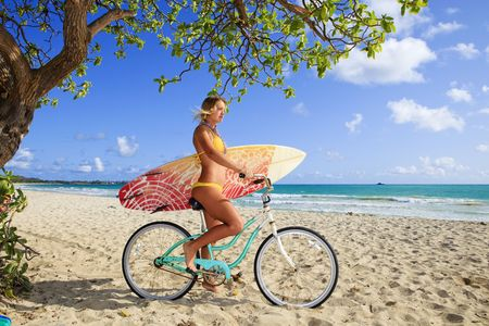 beautiful young girl on her bicycle with surfboard at kailua beach, hawaii photo