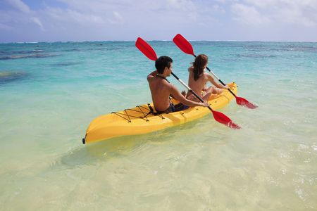 young couple kayaking in hawaii photo