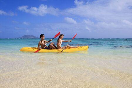 young couple kayaking in hawaii photo
