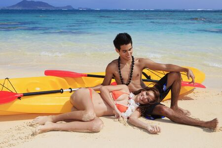 young couple on the beach in hawaii with their kayak photo